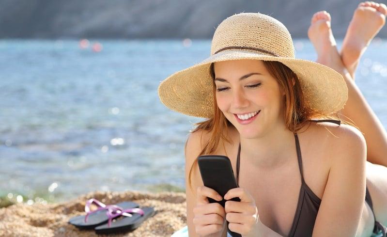 Menina usando celular em praia