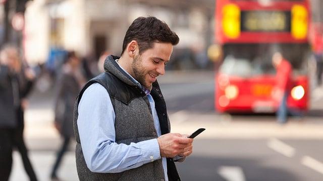 Homem usando celular na rua