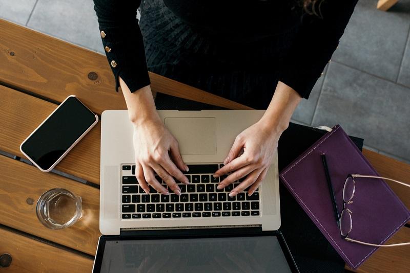 Menina usando o computador para fazer remessa internacional
