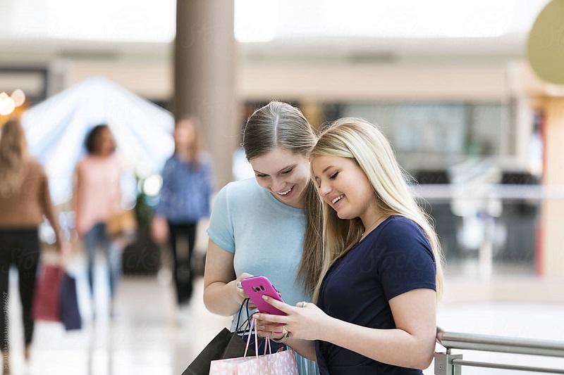Amigas usando o celular em shopping